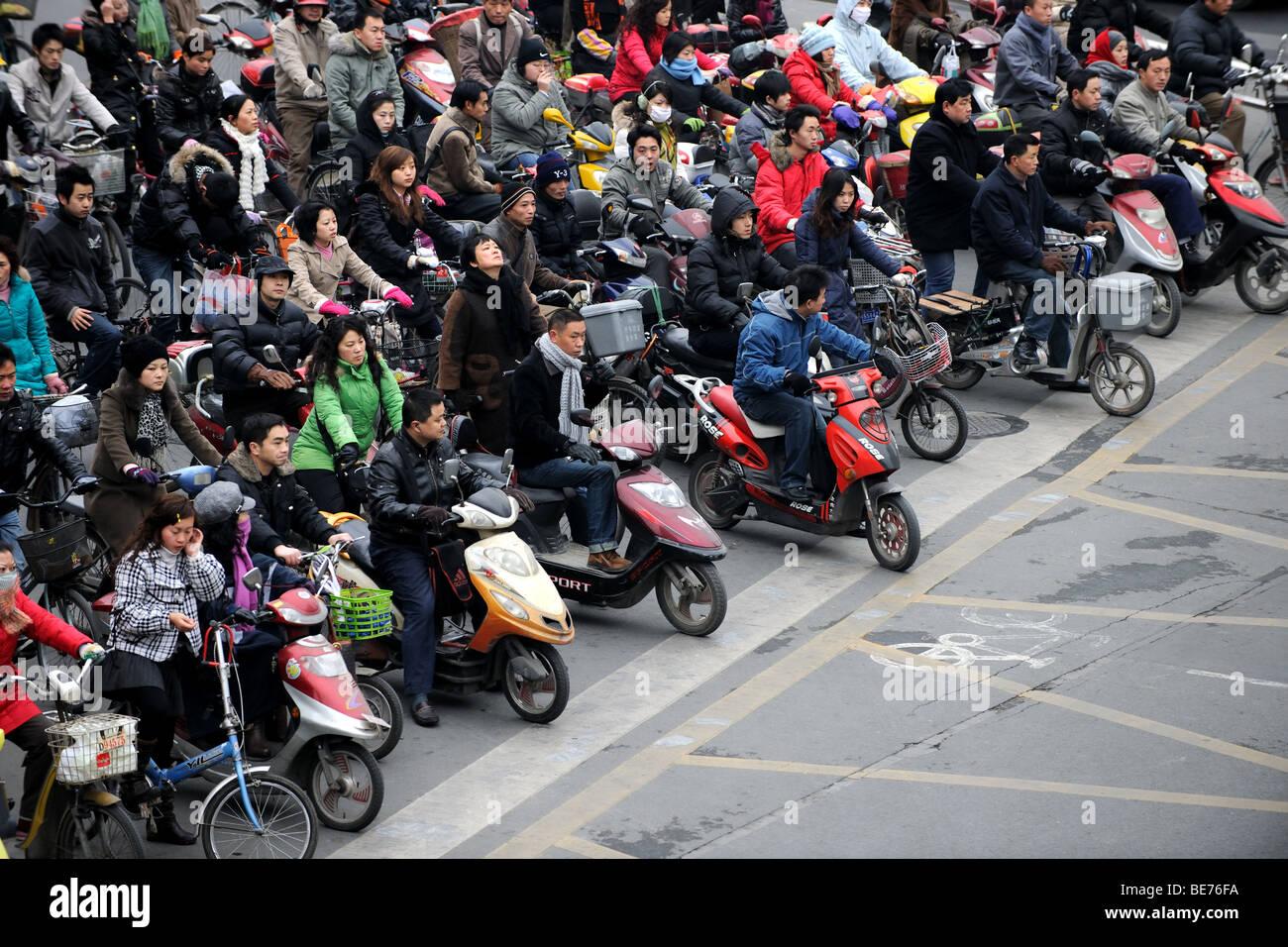 Multitud de bicicletas y motos cruzando en Shanghai, China Foto de stock