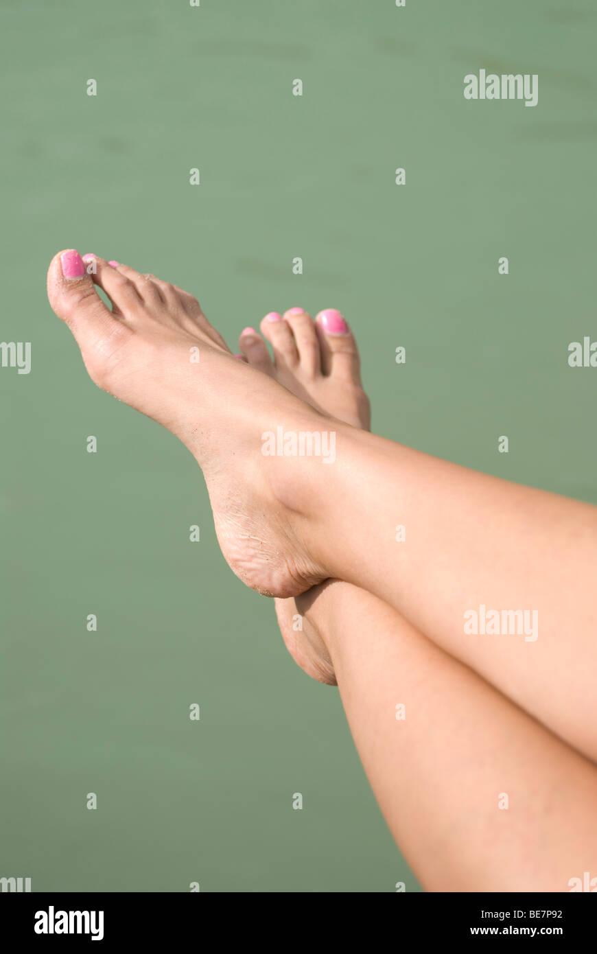 Las piernas de una mujer con esmalte de uñas de color rosa y verde ...