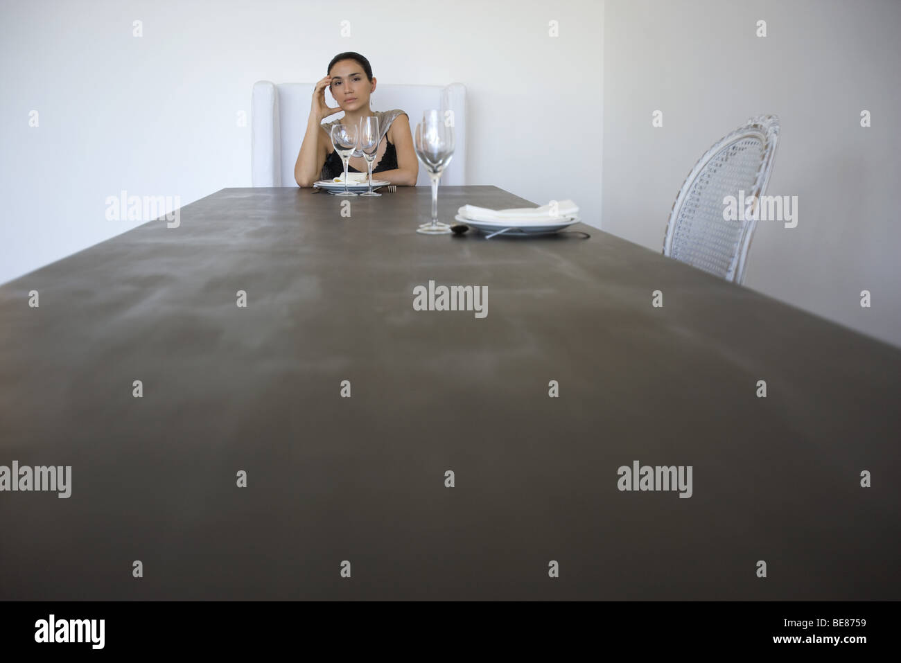 Mujer sentada sola en una mesa para dos, sosteniendo la cabeza Foto de stock