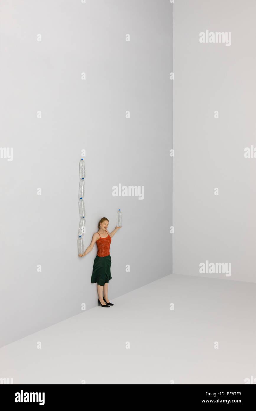 Equilibrio de mujer en una mano tall pila de botellas de agua, una botella en otra parte Imagen De Stock