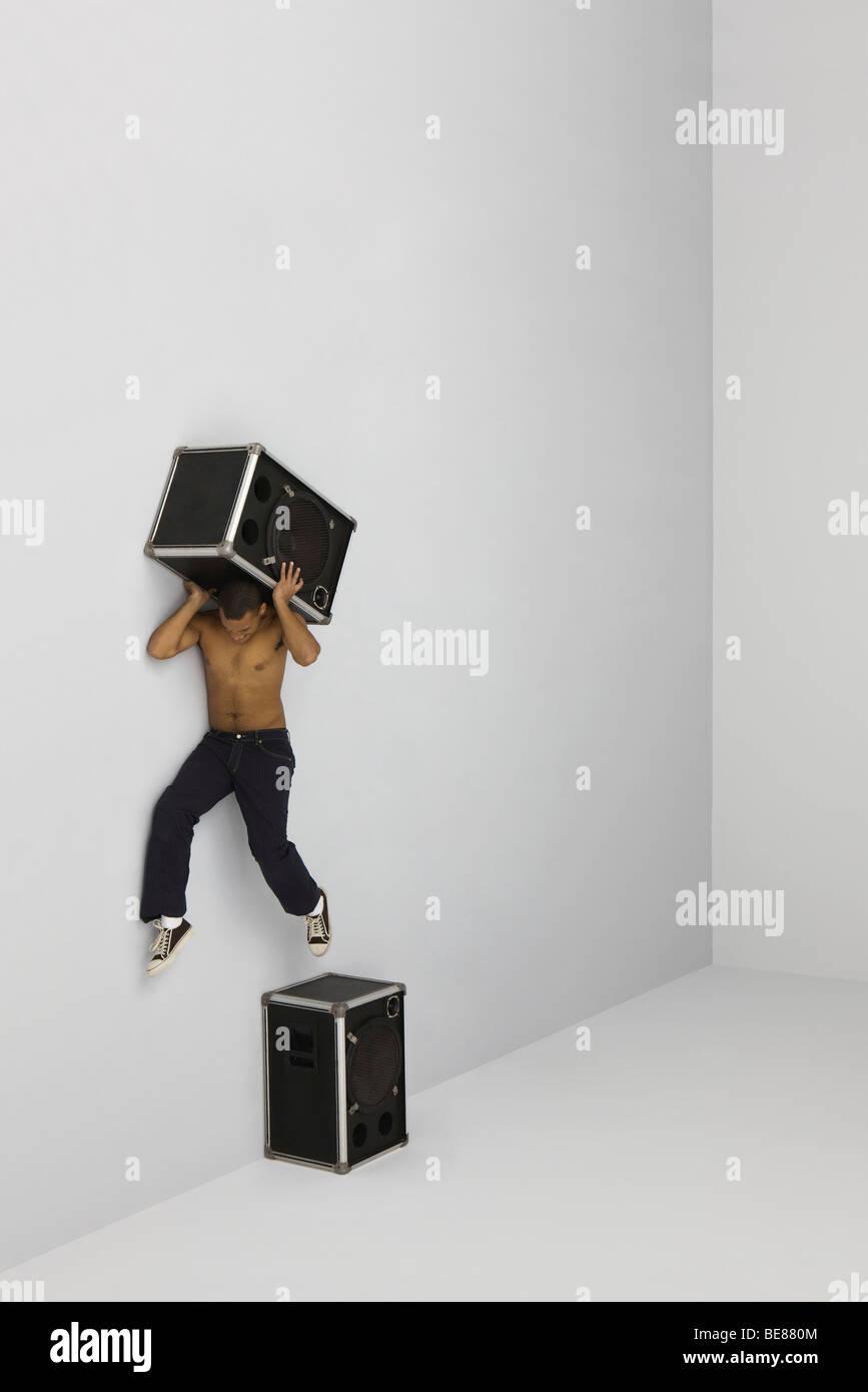 Hombre brincando de perca encima orador llevar segundo orador sobre los hombros Imagen De Stock