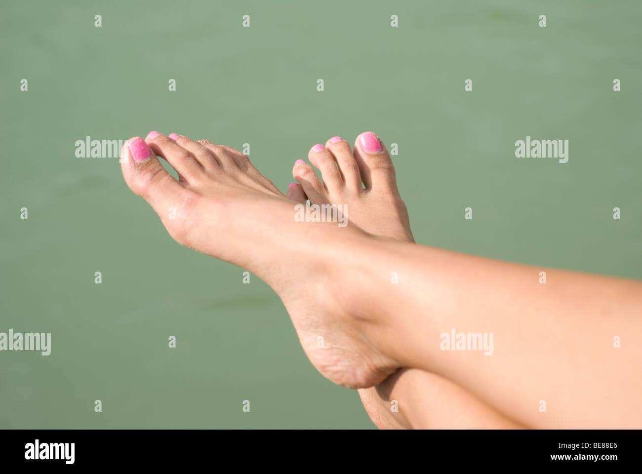 Mujer piernas y esmalte de uñas de color rosa verde mar de agua Lake ...