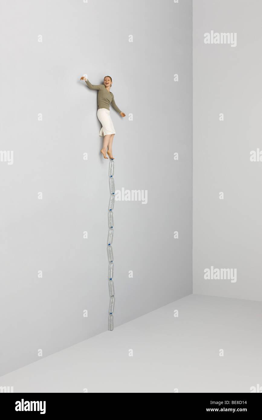 Mujer de equilibrio en un pie sobre la parte superior de la pila de botellas de agua Imagen De Stock