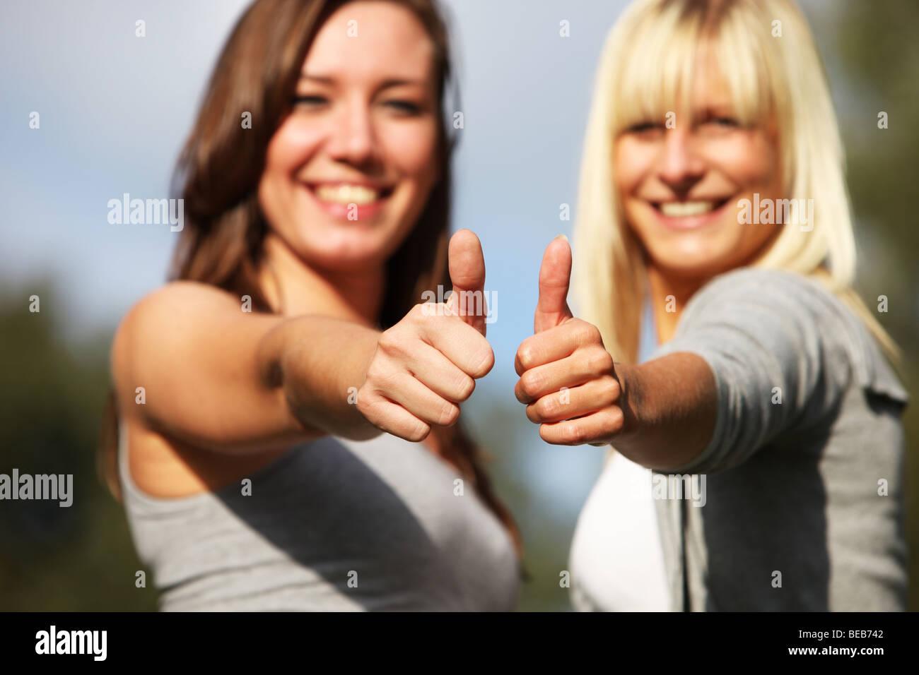 Dos jóvenes mujeres riendo positiva- de cerca - desde los pulgares. Imagen De Stock