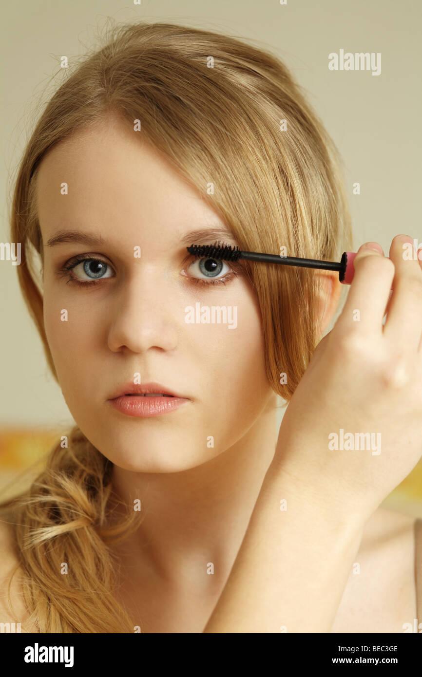 Adolescente aplicar la máscara en las pestañas. Imagen De Stock