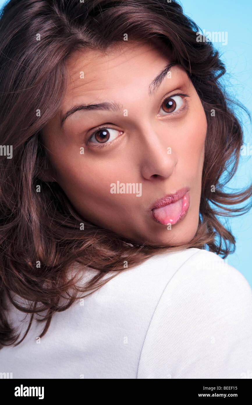 Impertinente morena mujer pegando su lengua fuera Imagen De Stock