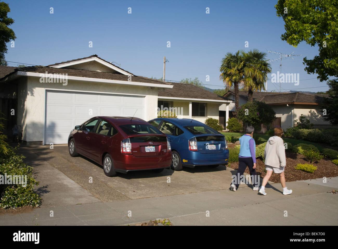 Dos personas que pasan dos Toyota Prius híbrido de coches que están estacionados en la cochera. Cupertino, Imagen De Stock