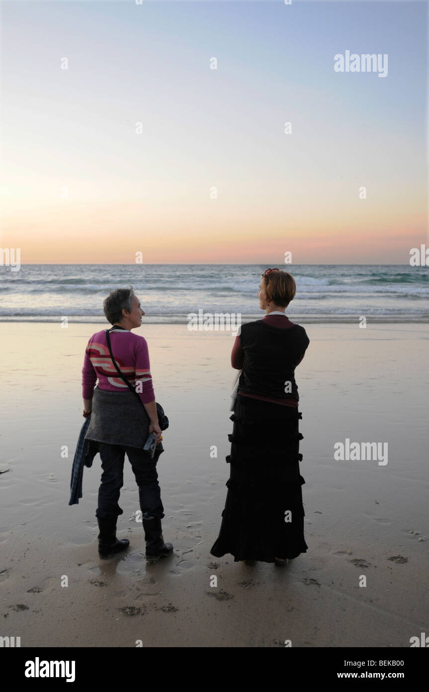 Dos amigos en un chat de Cornualles playa en el atardecer. Imagen De Stock