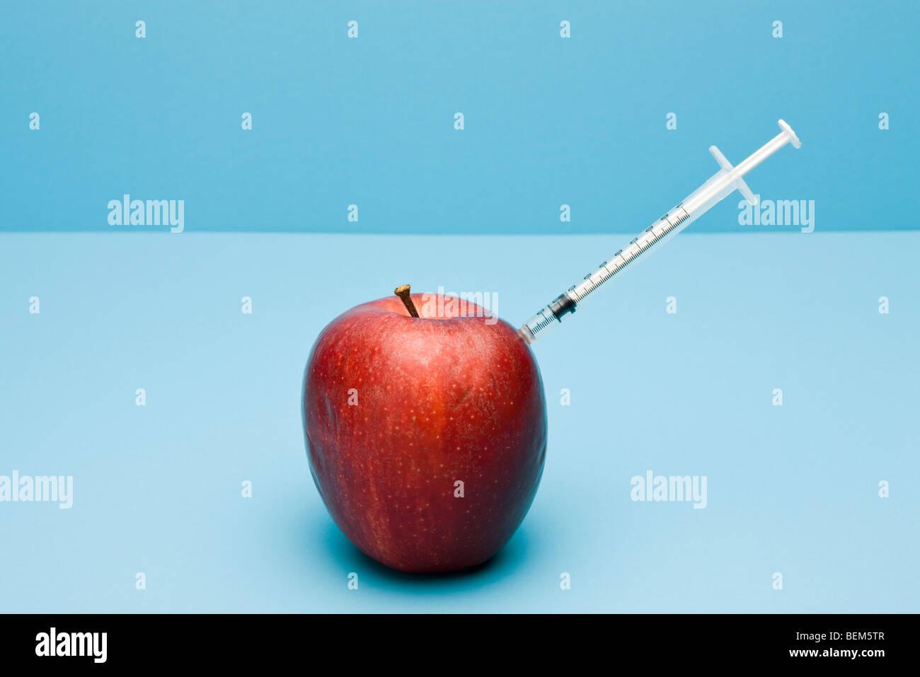 Concepto de alimentos, jeringa saliendo de apple Imagen De Stock
