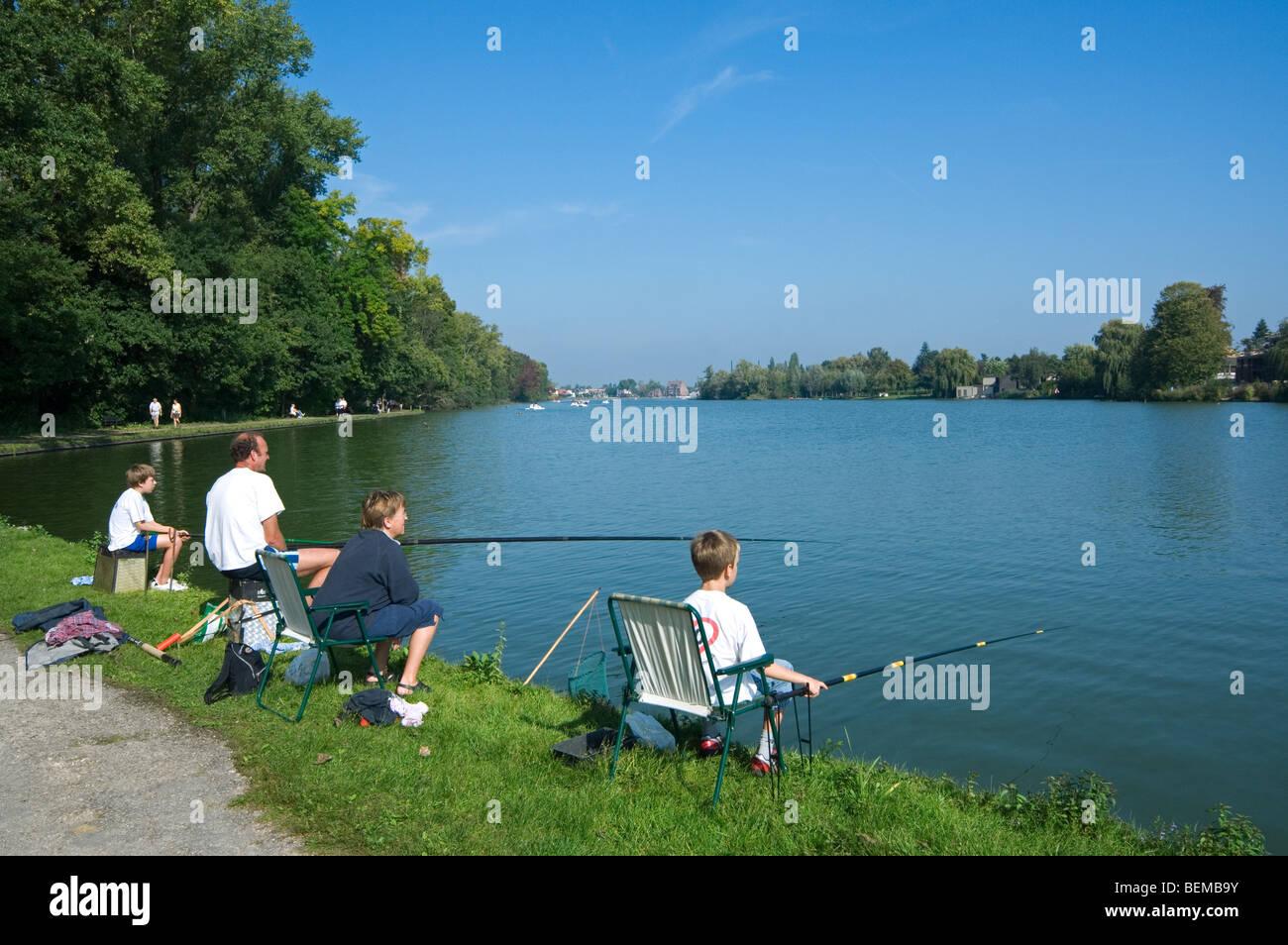 Familia, padre e hijos con cañas de pesca pesca deportiva en el lago Donkmeer, Flandes Oriental, Bélgica Imagen De Stock