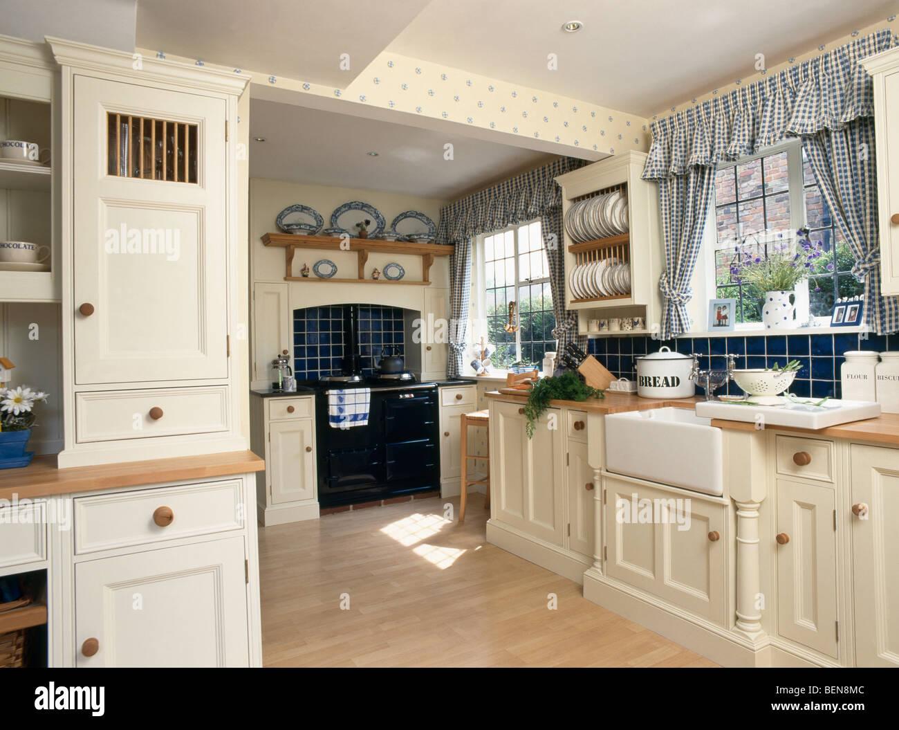 Cortinas en la ventana azul marcada en el país cocina equipada con ...