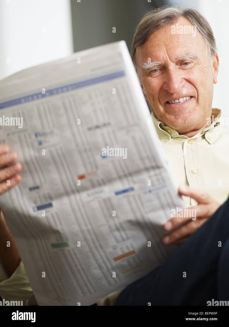 Altos hombre Leyendo listas de valores y sonriente Imagen De Stock