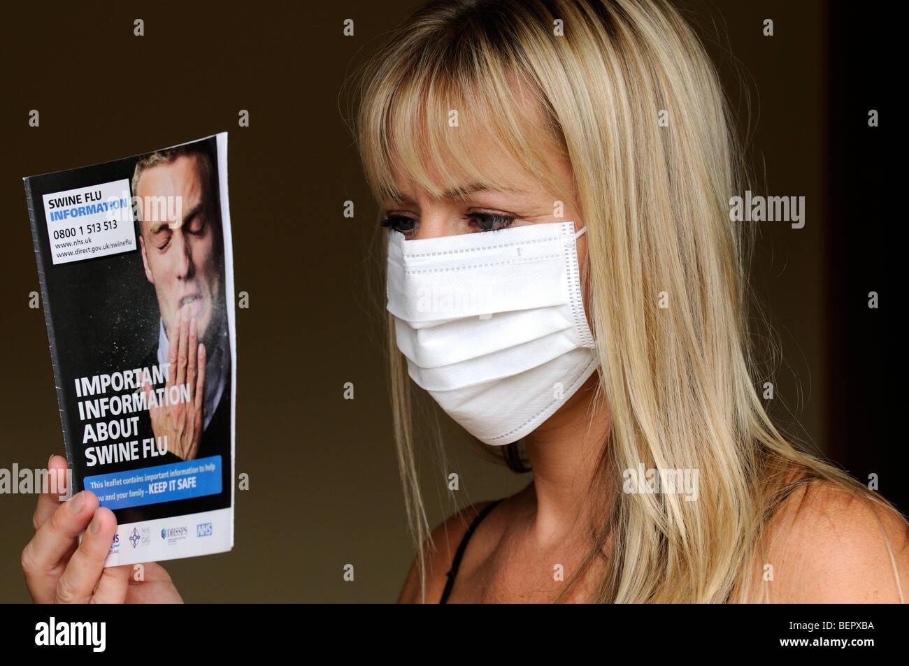 Retrato de una mujer que llevaba una máscara de médico y leer el folleto de información de la gripe porcina Foto de stock