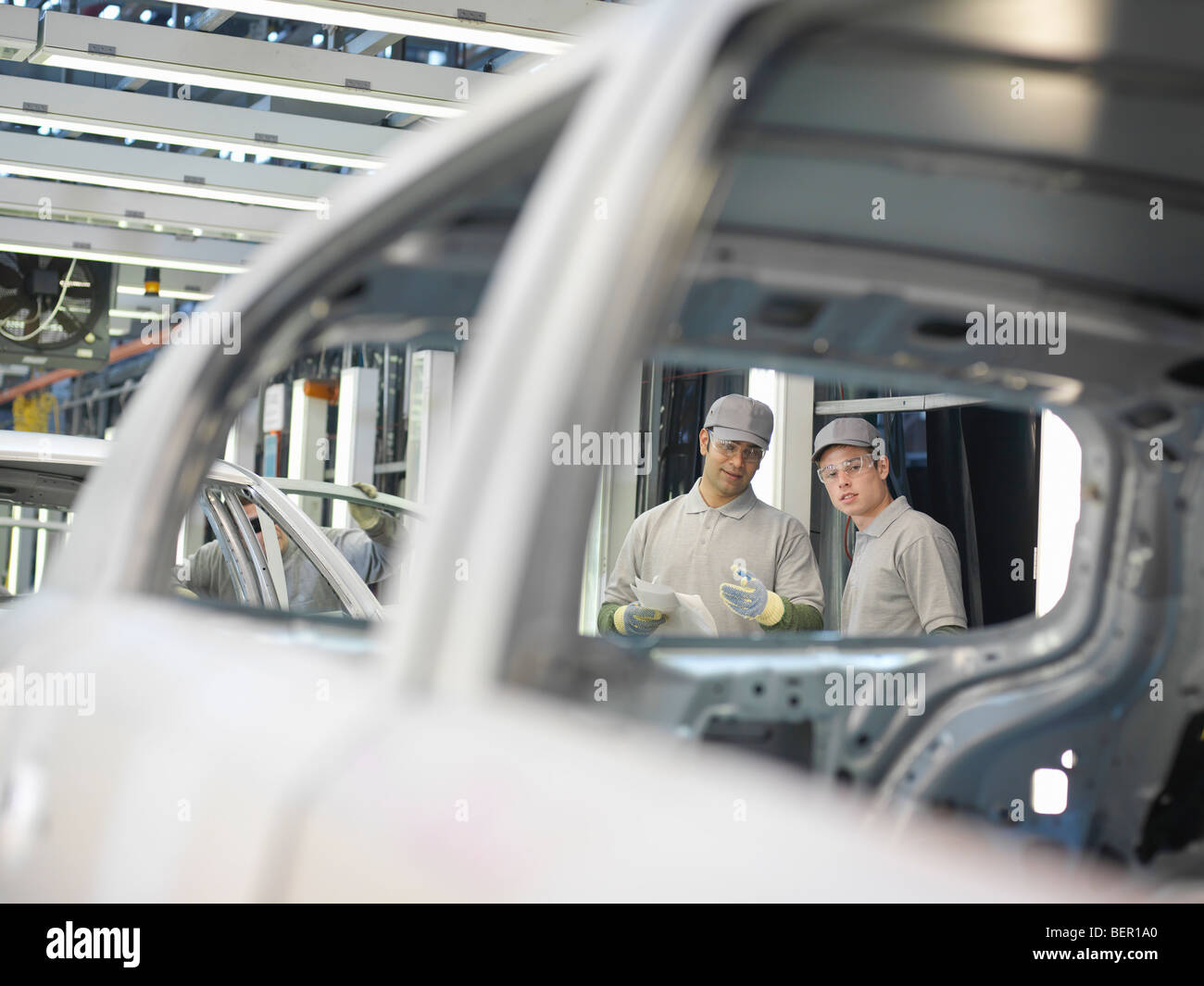 Trabajadores de la fábrica de automóviles de hablar de coches Imagen De Stock