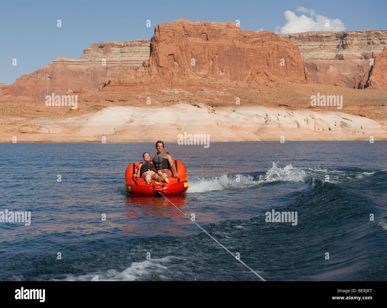 Una pareja se monta sobre un remolque hinchable mientras es remolcado detrás de un bote en el lago Powell, en Utah, EE.UU.. Foto de stock