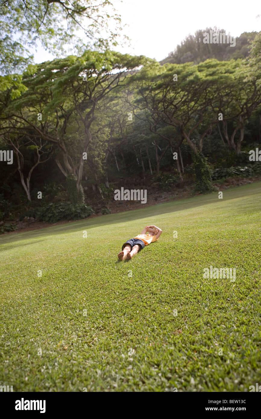 Niño sentar y descansar en un campo de hierba, parque público, Honolulu, Hawai Imagen De Stock
