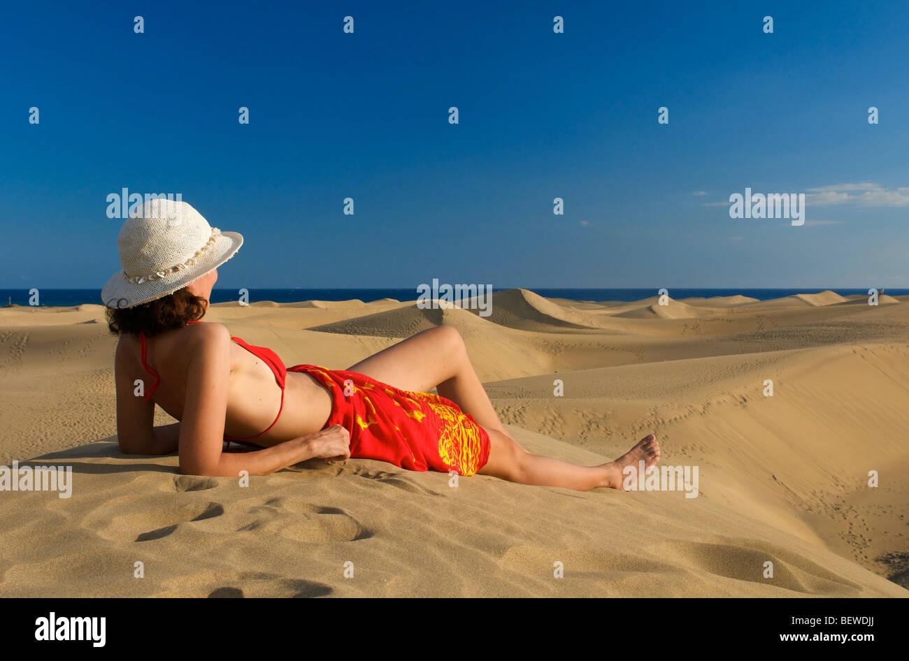 Mujer acostada sobre una duna de arena mirando el mar, Maspalomas, Gran Canaria, España, vista lateral Imagen De Stock