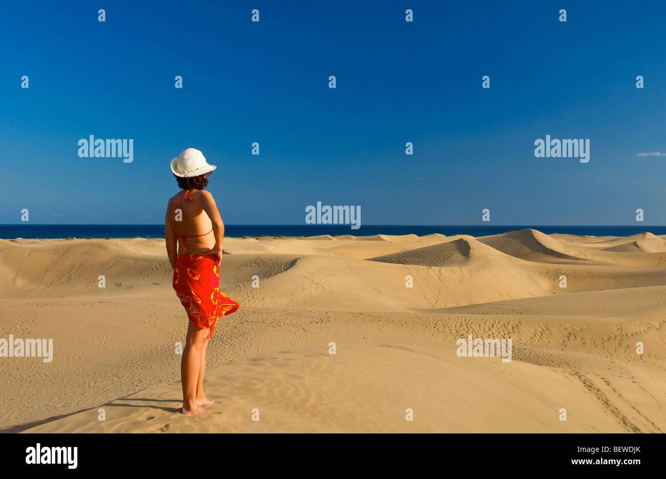 Mujer de pie sobre una duna de arena mirando el mar, Maspalomas, Gran Canaria, España, vista trasera Imagen De Stock