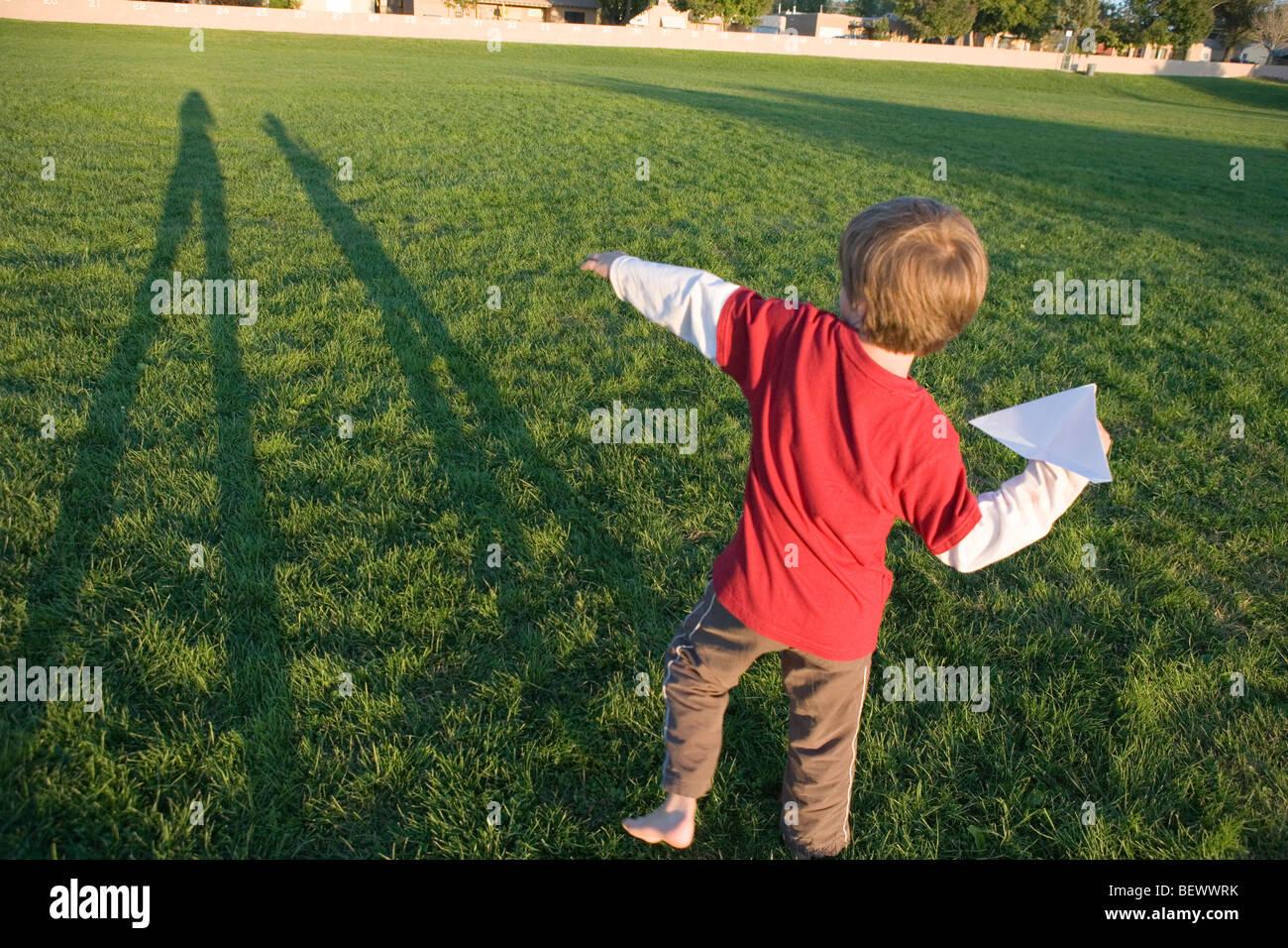 Niño de siete años preparándose para lanzar su avión de papel en un parque Imagen De Stock