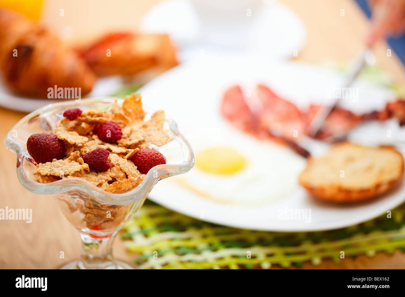 Delicioso desayuno servido. Las hojuelas de maíz con bayas, huevo frito, bacon, tostadas, croissants, zumo Imagen De Stock