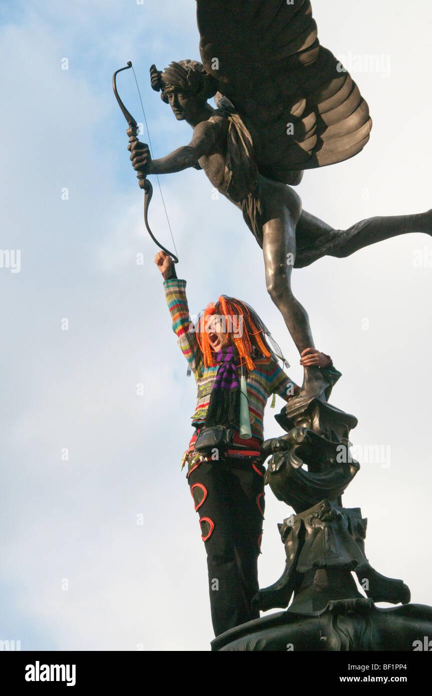 Recuperar el amor Valentines Party en Piccadilly Circus celebra el amor contra el consumismo. Mujer sube con Eros Foto de stock