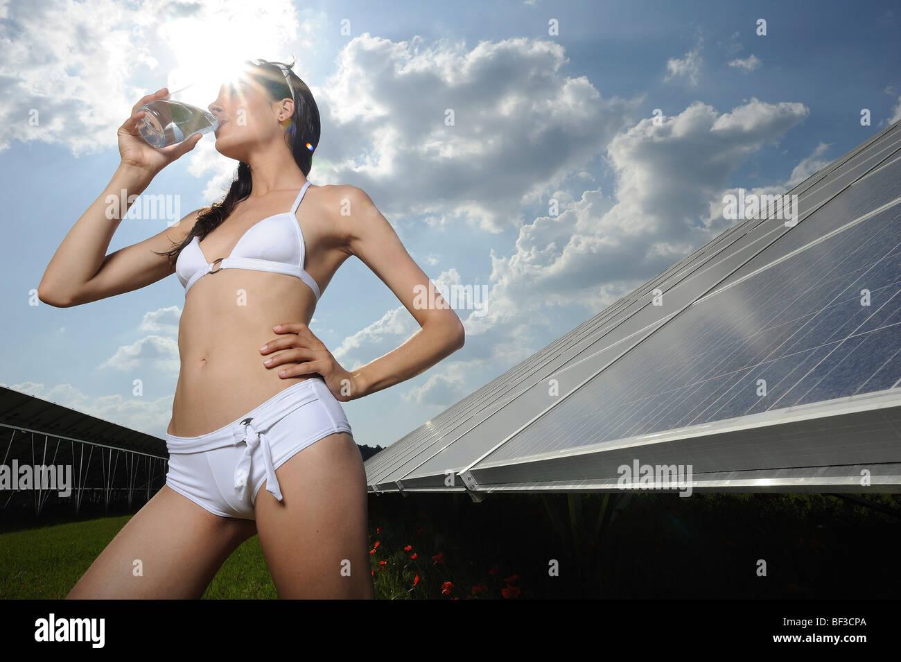Mujer de agua potable cerca de panel solar Imagen De Stock