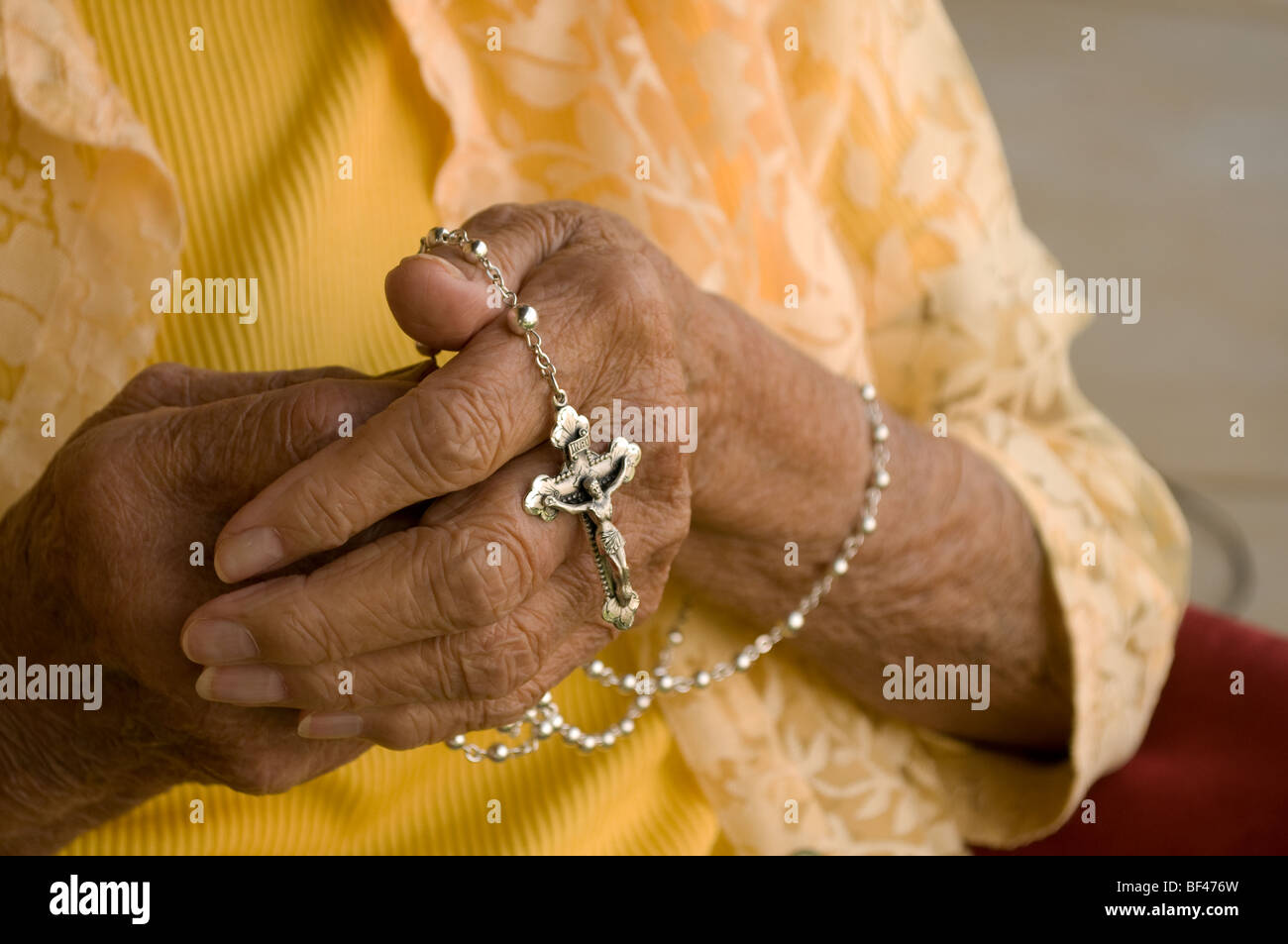 Ancianos caucasian manos sosteniendo un rosario de plata Imagen De Stock