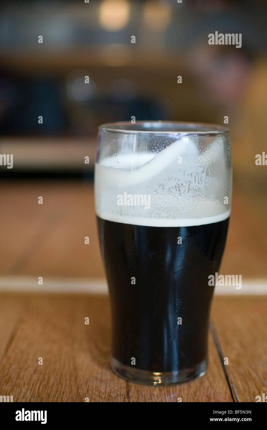 Una pinta de cerveza negra real ale sentado en una mesa de pub Foto de stock