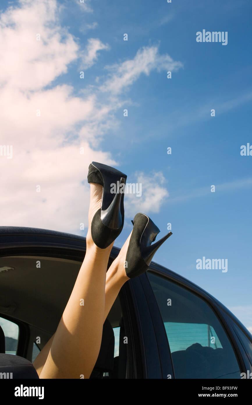 Los pies y las piernas de una mujer vistiendo negro zapatos stilletto sobresalen de la ventanilla Imagen De Stock