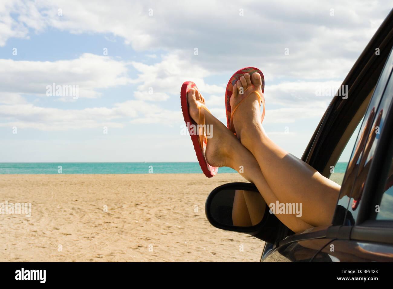 Los pies y las piernas de una mujer en naranja flip flops que sobresalen de la ventanilla en la parte delantera Imagen De Stock