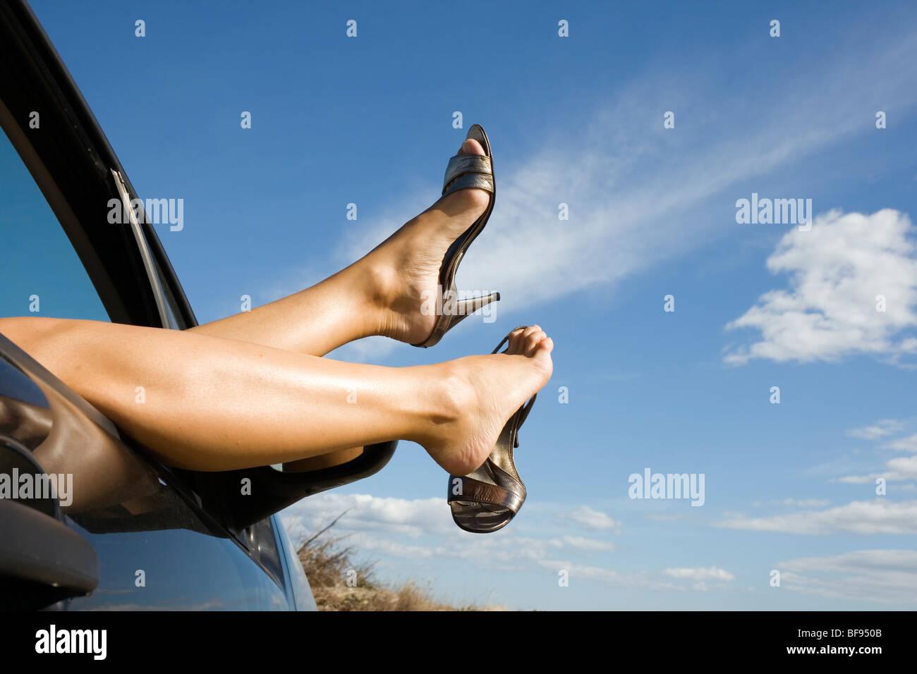 Piernas y pies de mujer vestidos de plata zapatos de tacón alto que sobresalen de la ventanilla. Imagen De Stock