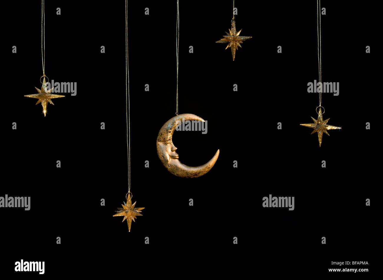 La luna y las estrellas brillantes de oro brillante colgando decoraciones de navidad contra un fondo negro Foto de stock