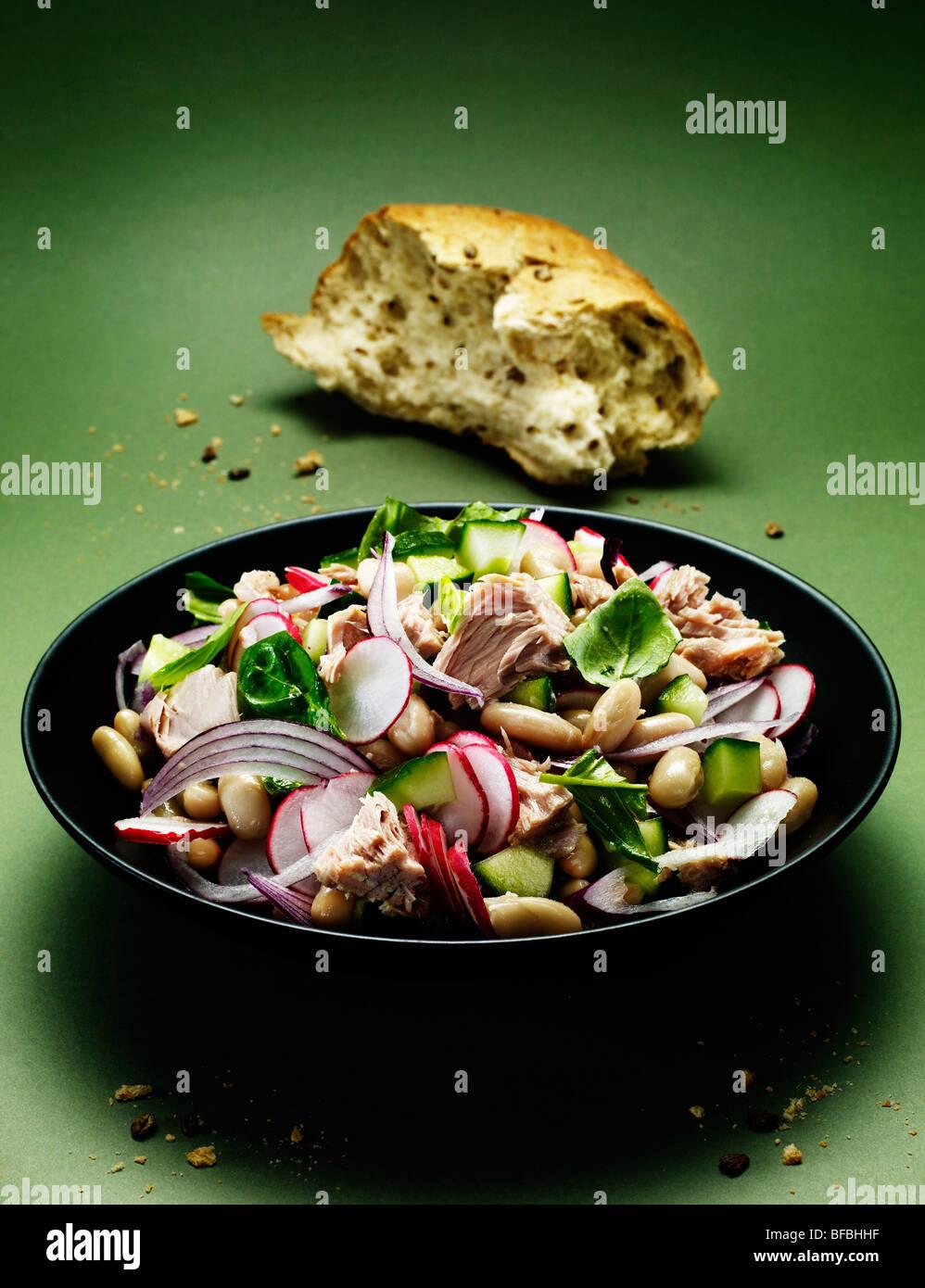 Ensalada de atún y cannellini, con cebolla roja, albahaca, rábano y pepino servidor con pan integrales. Imagen De Stock