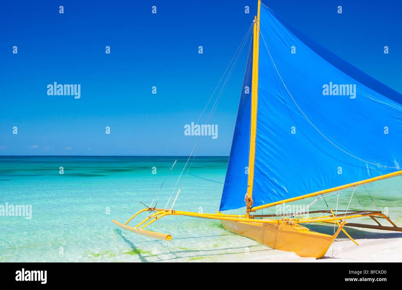 Barco amarillo con azul navegar en aguas poco profundas Boracay; las Visayas, Filipinas Foto de stock