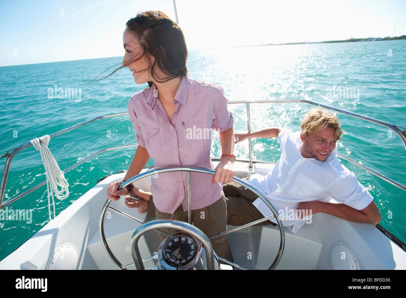 Una mujer piloto una embarcación de Florida, mientras que un hombre se sienta cerca. Foto de stock