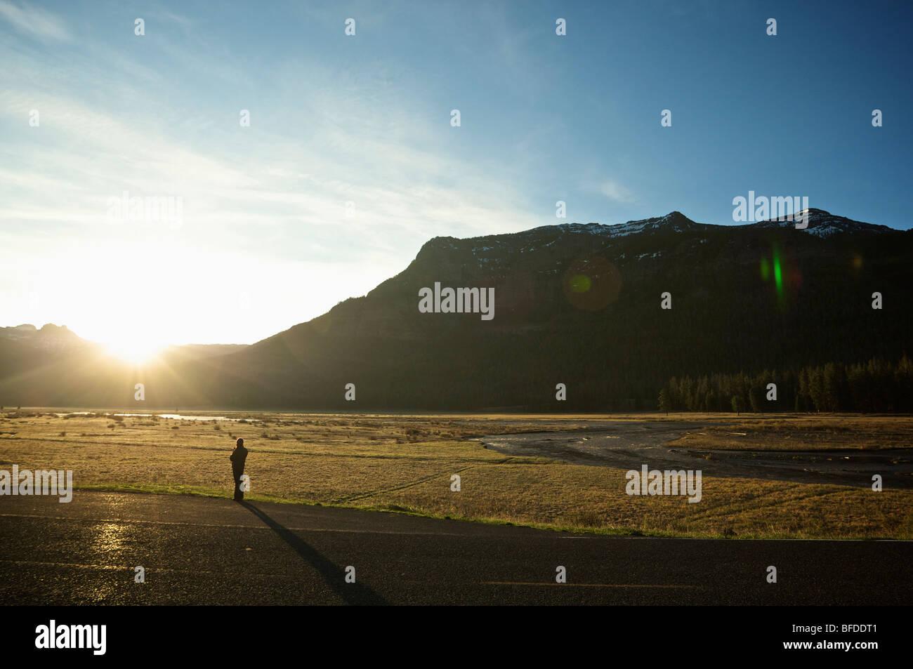 Una mujer bebe café y observa el amanecer desde la carretera junto a un campo en el Parque Nacional de Yellowstone. Imagen De Stock