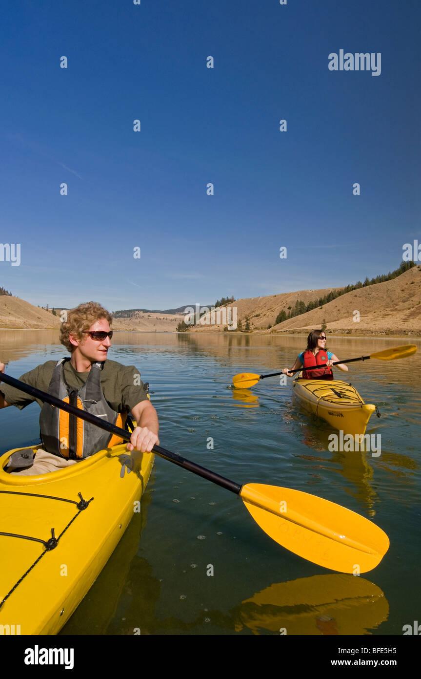 Una joven pareja disfruta de un espectacular día de kayak en el lago Trapp, justo al sur de Kamloops, British Imagen De Stock