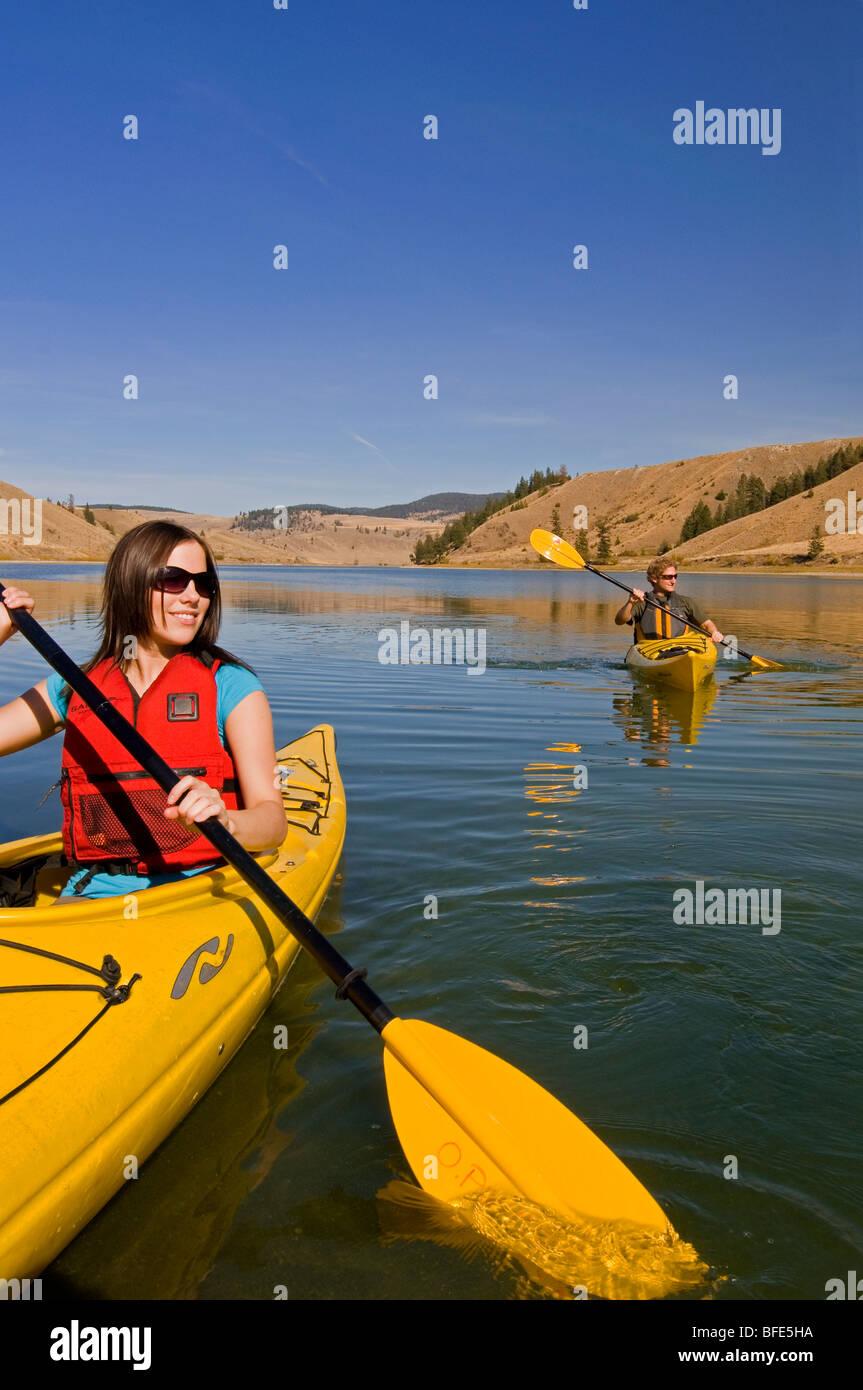 Una joven pareja disfruta de una impresionante día mientras el kayak en el lago Trapp, justo al sur de Kamloops, Imagen De Stock