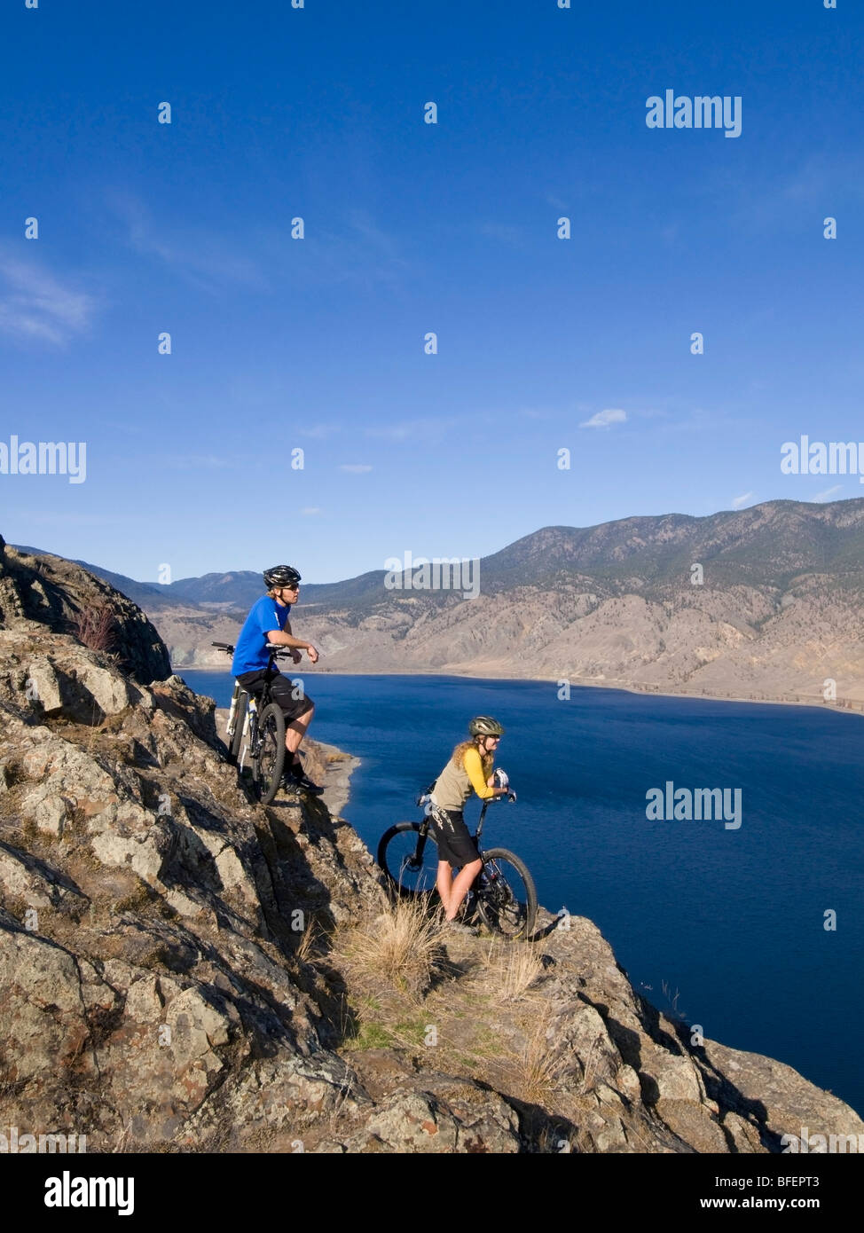 Pareja joven disfrutando de la vista de Kamloops Lake mientras el ciclismo de montaña en un hermoso día Imagen De Stock
