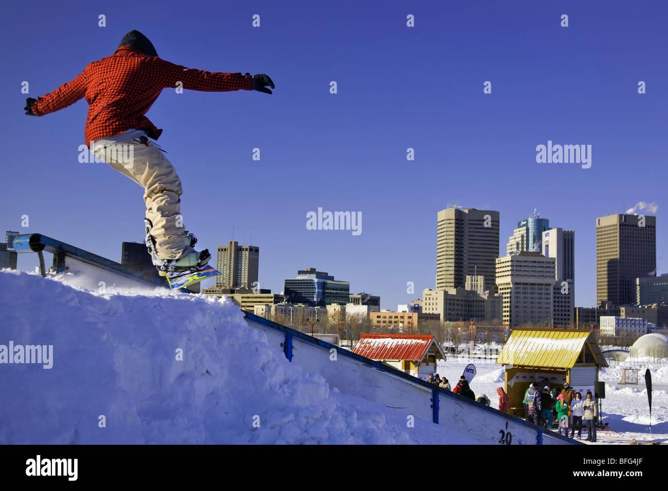 Varón adolescente snowboarder en horquillas Winter Park en el centro de Winnipeg. Parte de la competencia de snowboard Snowjam. Winnipeg Manitob Foto de stock