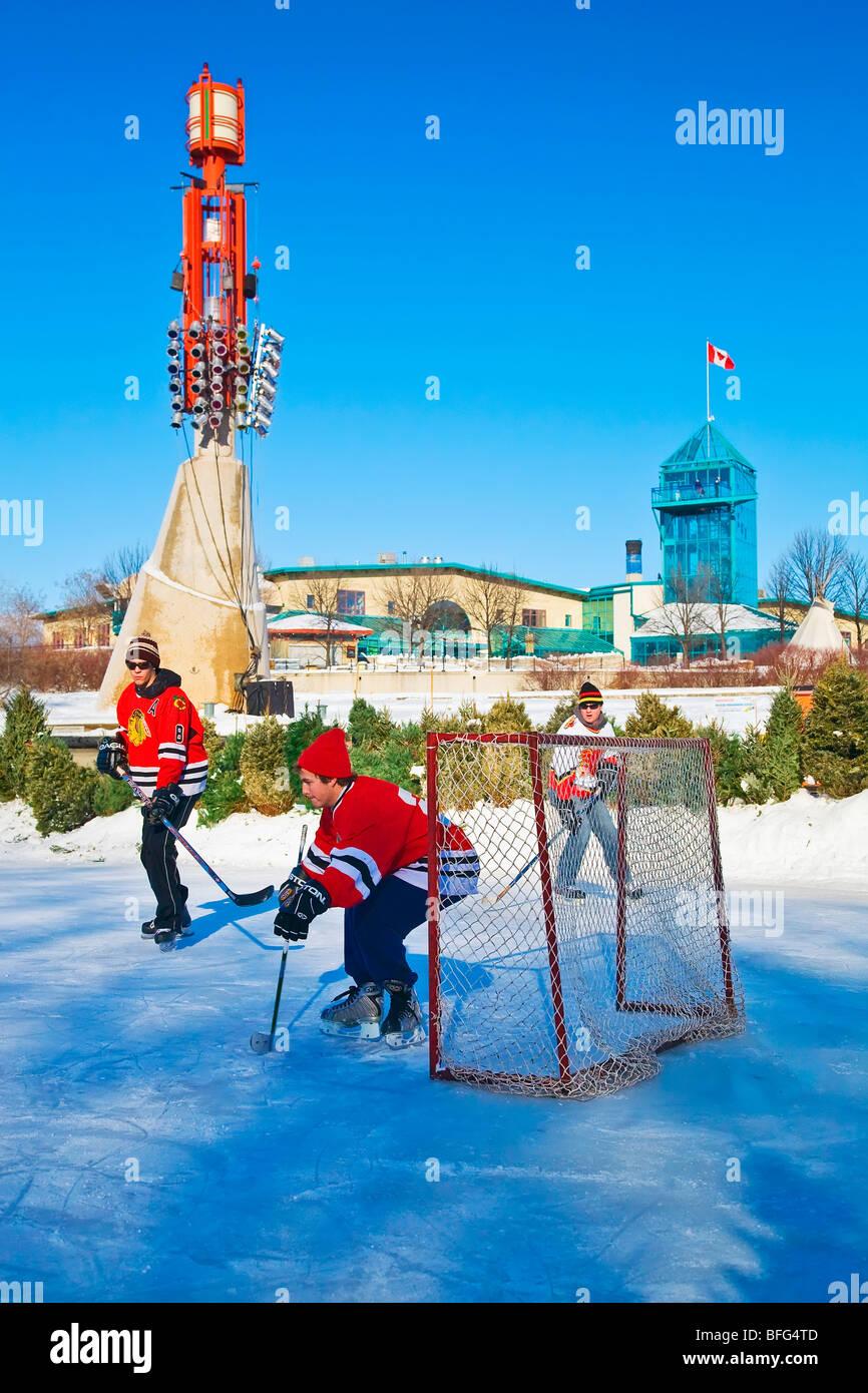 Los hombres jóvenes jugar hockey sobre hielo en el Assiniboine River, en las horquillas en el centro de Winnipeg, Manitoba, Canadá. Foto de stock