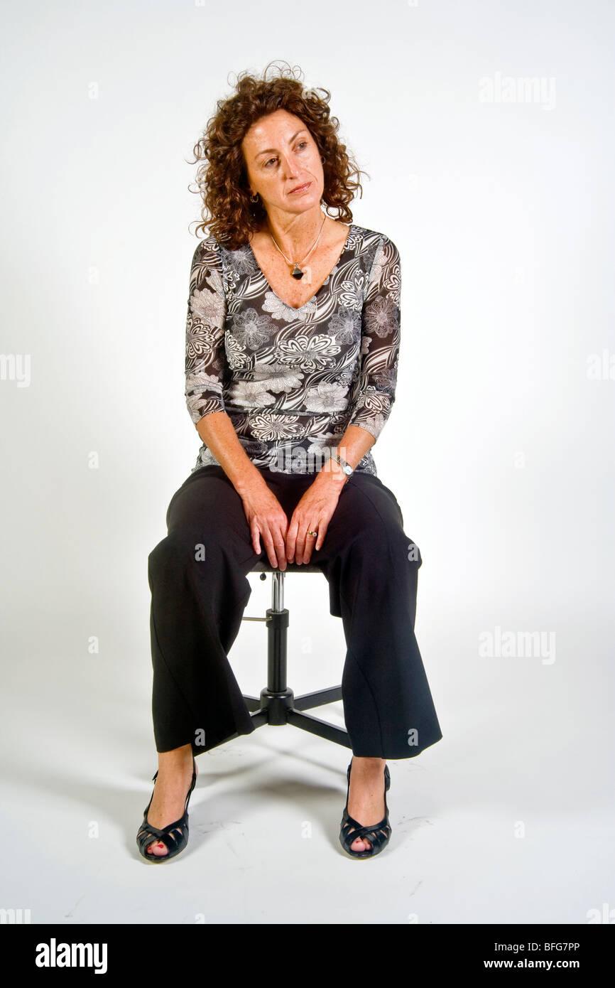 """Sentado con las piernas indica un estado de ánimo relajado y abierto en esta mujer en términos de """"lenguaje Imagen De Stock"""