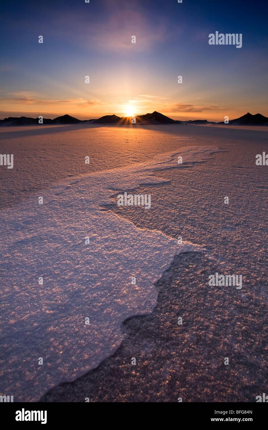 El sol detrás de las montañas de hielo flotante en el Lago Huron en Bayfield, Ontario, Canadá Foto de stock