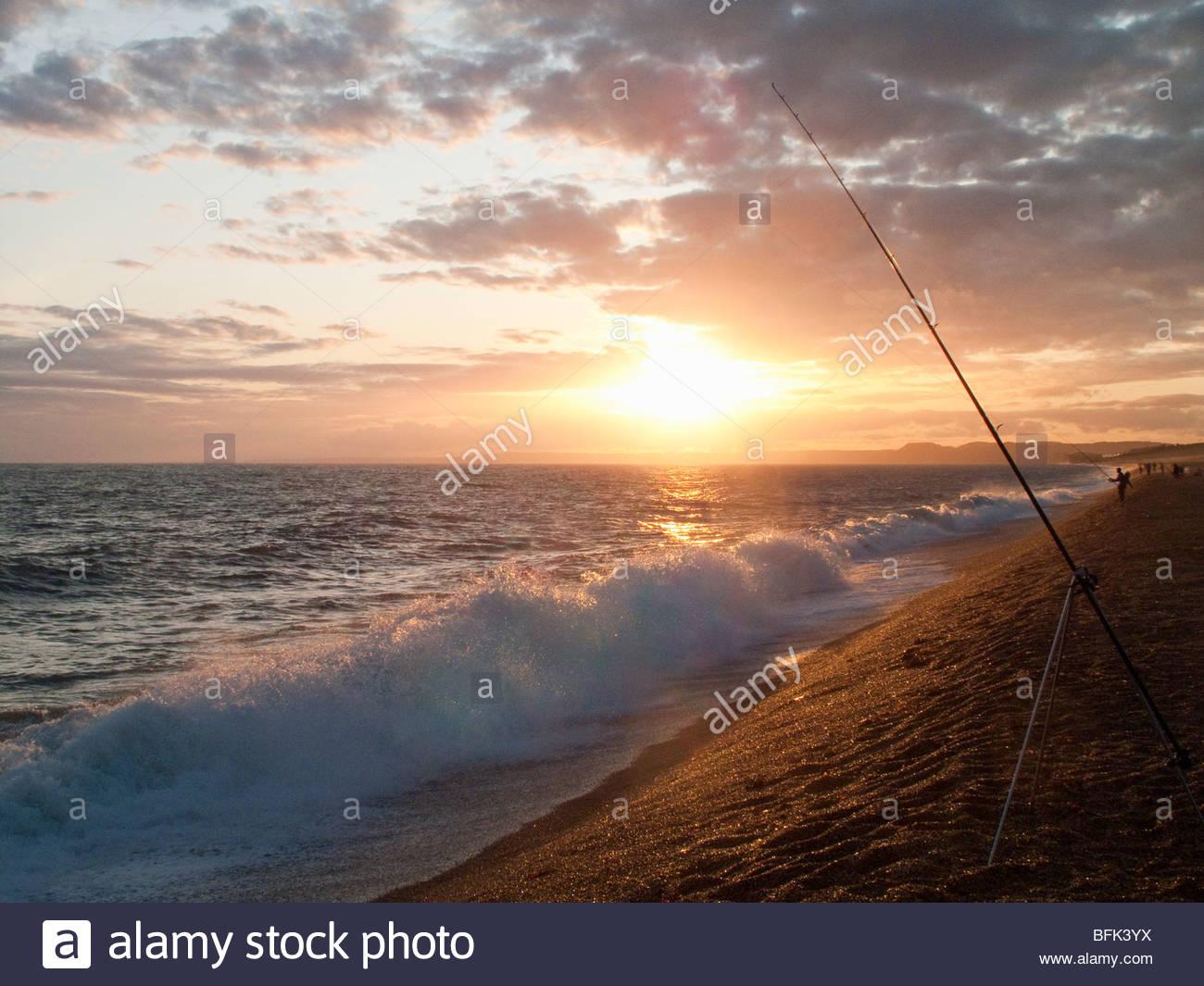 Tranquilo y puesta de sol en el horizonte sobre el océano con caña de pescar en primer plano Foto de stock