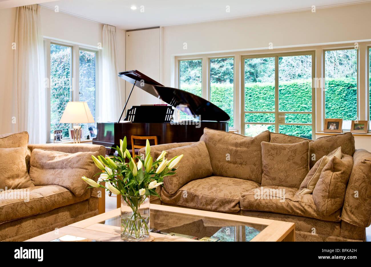 Un elegante salón moderno, inteligente, salón o salón con piano y un jarrón de azucenas Imagen De Stock