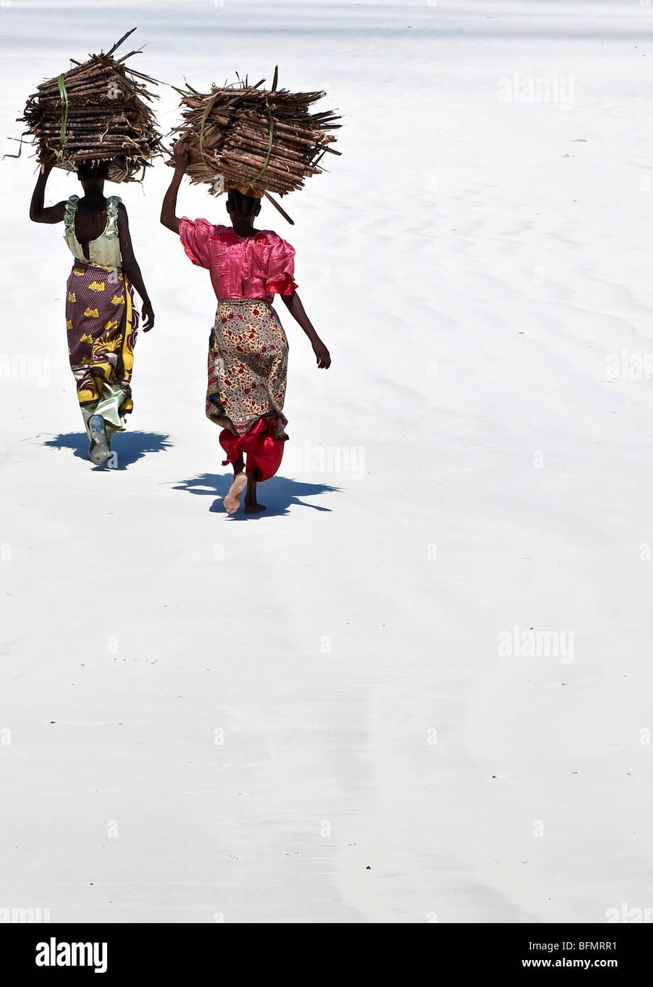 Mombasa, Kenia. Las mujeres llevan sobre sus cabezas de makuti (frondas de palma de coco desecado utilizado como Imagen De Stock