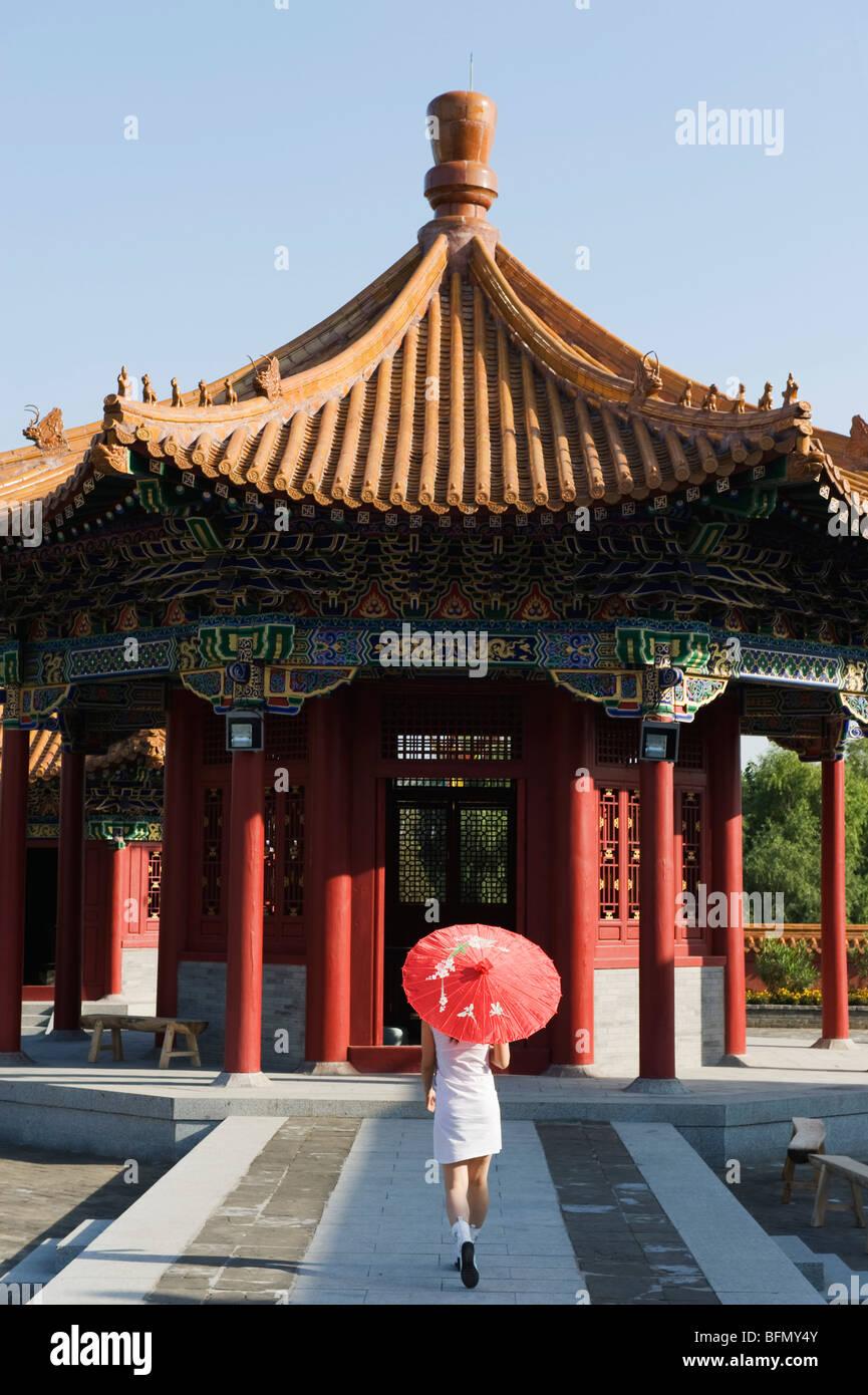 China, Beijing, Minorías Étnicas Park, una niña con sombrilla en un pabellón Imagen De Stock