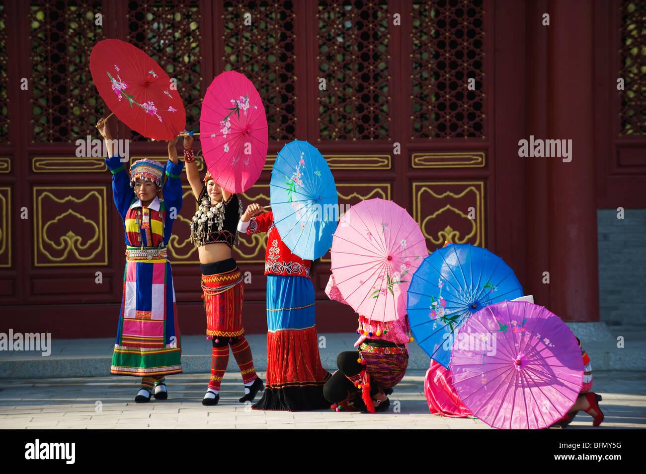 China, Beijing, Parque de las minorías étnicas, las niñas bailando con sombrillas Imagen De Stock