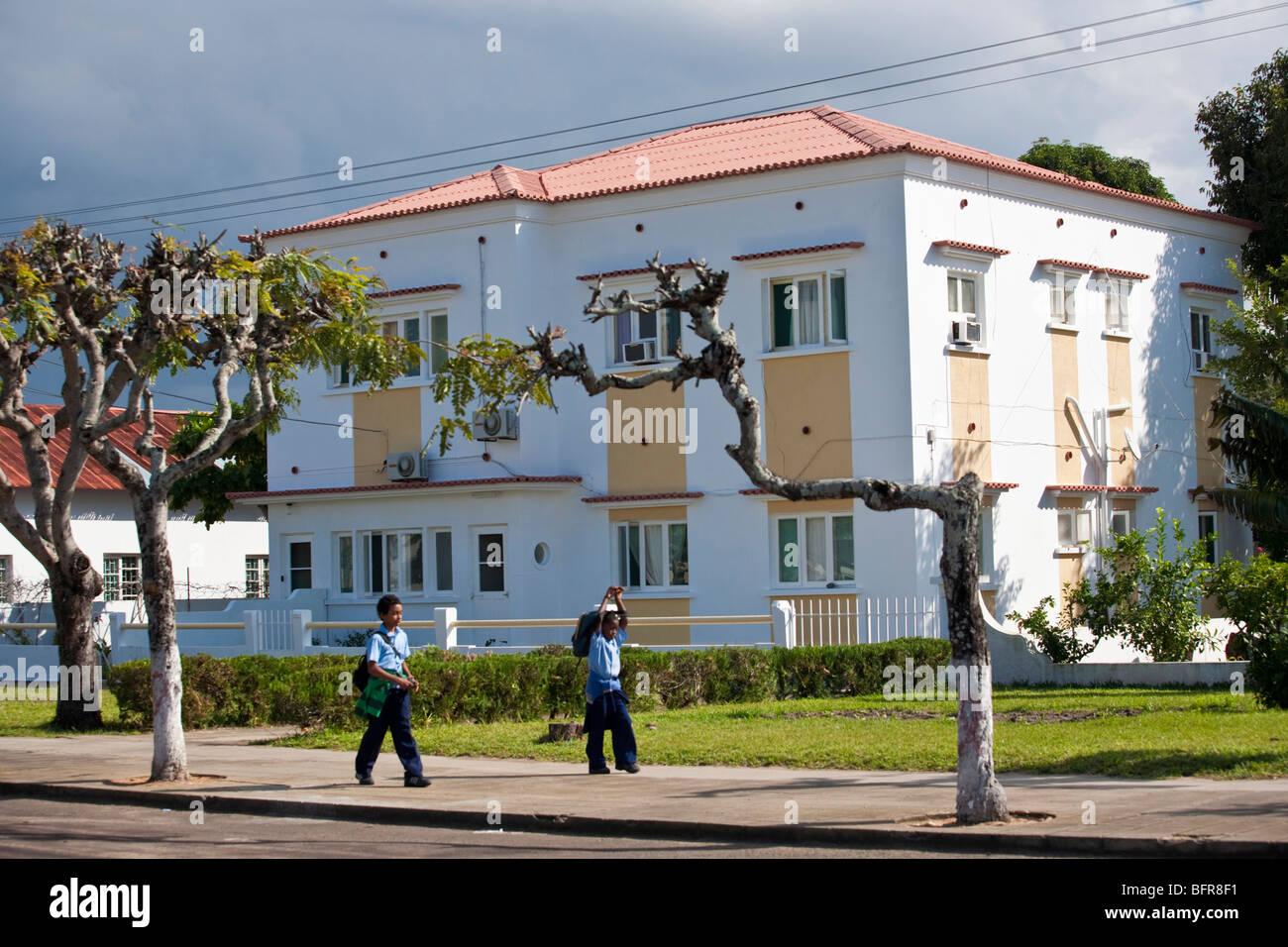 Edificio blanco con colegiales pasando Imagen De Stock