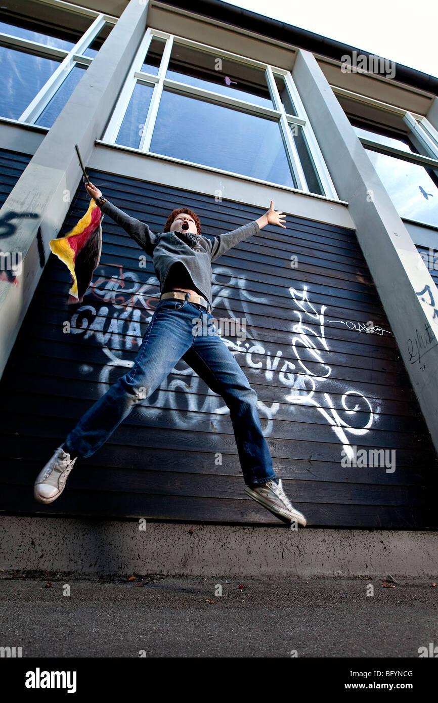Ángulo de visión baja de joven con la bandera saltando Imagen De Stock